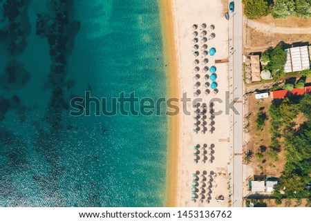 Aerial view from a drone to the sea sandy beach with sun beds and umbrellas for tourists in Greece. Turquoise clear water on the beach on a sunny summer day. Tourist season #1453136762