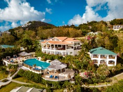 aerial view from above at the tropical island St Lucia with hotels and buildings in the mountains, drone view