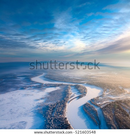 Aerial view from above forest river during cold winter day. Hoarfrost is on trees. A winter forest lights in the rays of low winter sun in a hard frost. Fancy clouds are stretching above frozen earth.