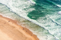 Aerial view from above of ocean, sea beach and water waves with people on sand shore with emphasis of the scale of people and nature. Surfers Paradise, Gold Coast, Queensland Australia