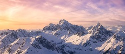 Aerial View from Airplane of Blue Snow Covered Canadian Mountain Landscape in Winter. Colorful Pink Sky Art Render. Tantalus Range near Squamish, North of Vancouver, British Columbia, Canada.