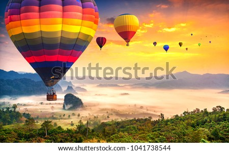 Aerial view from colorful hot air balloons flying over with the mist at Phu Langka national park in sunrise time,  Phayao province in Thailand.