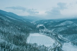 Aerial view from drone above mountain gorge between mountain peaks in winter time in snowy weather