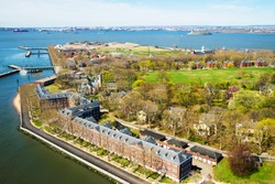 Aerial view from helicopter on Governors Island in Upper New York Bay. New York City, NYC, USA. Liberty Island is on the background