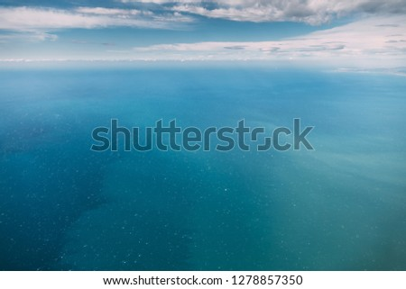 Aerial View From High Altitude Flight Of Aircraft On Sea Ocean Surface. Natural Sea Background.