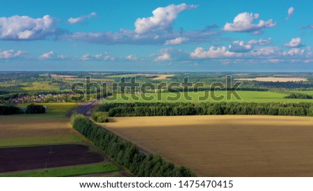 Aerial view from quadrcopter drone of a landscape with a green fields and wheat fields. The fields are divided by roads. Aerial rural scene at sunny day