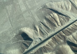 Aerial view geometric drawing line geoglyph spiral on soil Nazca (Nasca) desert Peru. Mysterious images on the earth ground possibly made by alien civilization for ancient irrigation system.