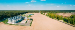 Aerial View Granary, Grain-drying Complex, Commercial Grain Or Seed Silos In Sunny Spring Rural Landscape. Corn Dryer Silos, Inland Grain Terminal, Grain Elevators Standing In A Field. Panorama.