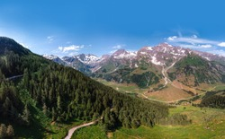 Aerial view Grossglockner Hochalpenstrasse, Alpine Road in Austria. Pine forest, sunny summer day, blue sky. Motorcyclists and travelers road. vacation and adventure, hiking and active lifestyle