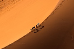 Aerial view group of people walking on the sand dune in the desert and sun gradually create beautiful scene.