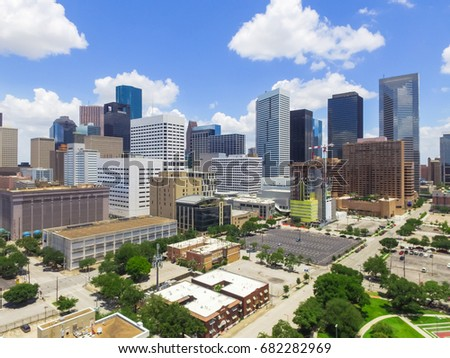 Aerial view Houston downtown against cloud blue sky with empty parking lot at weekends and background of skyscrapers/high-rises in the business district area. Architecture and travel background