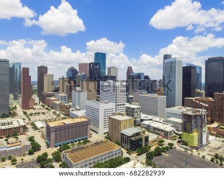 Aerial view Houston downtown against cloud blue sky with empty parking lot at weekends, building/high-rises under construction and background of skyscrapers in the business district area