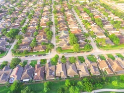 Aerial view huge park near residential houses in Houston, Texas, USA. Green urban recreation with long pathway surrounds with green tree. Tightly packed homes neighborhood and driveways flyover