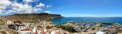 Aerial view, in panoramic format, of Puerto de Mogan, in Gran Canaria, Spain, showing, buildings, beach, bay, sea and nearby hills on the coast