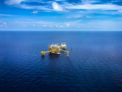 Aerial view industrial offshore oil and rig drilling platform in the gulf with blue sky,Copy space.