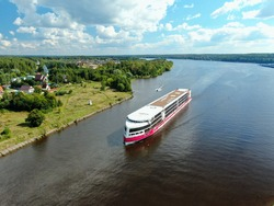 Aerial view journey by passenger cruise ship on the river. Beautiful panoramic landscape from a height ship sails along a large river against the background of water and clouds