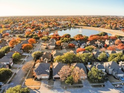 Aerial view lakeside houses neighborhood with colorful autumn leaves. Flyover row of single-family houses with attached garage near lake with water fountain in Flower Mound, Texas, USA