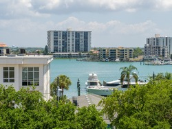 Aerial view looking down Clearwater, Florida harbor view with yacht, palm trees, and condo buildings.