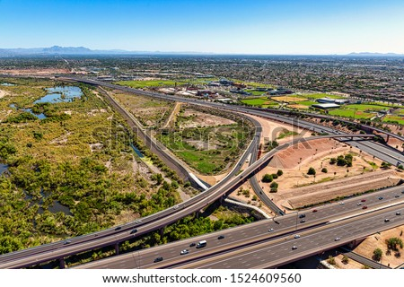 Aerial view looking from the northwest to the southeast of the Loop 101 & 202 freeways at the Salt River in Mesa, Arizona with bike path, soccer fields  and ball park in the area #1524609560