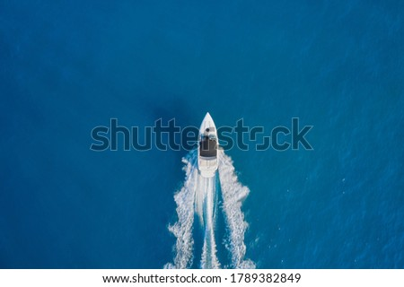 Aerial view luxury motor boat. Motor boat in the sea. Drone view of a boat sailing. Travel - image. Top view of a white boat sailing to the blue sea.