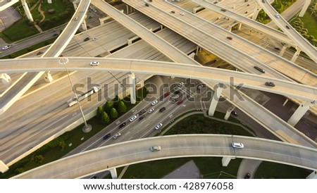 Aerial view massive highway intersection, stack interchange with elevated road junction overpass at late afternoon in Houston, Texas. This five-level freeway interchange carry heavy traffic, panorama. #428976058