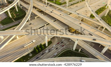 Aerial view massive highway intersection, stack interchange with elevated road junction overpass at late afternoon in Houston, Texas. This five-level freeway interchange carry heavy traffic, panorama. #428976229