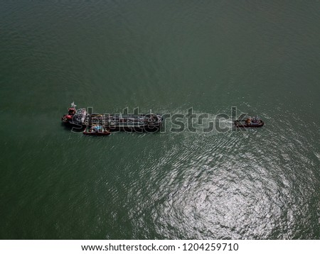 Aerial view of a barge and tugboat. Barge is a flat-bottomed ship, built mainly for river and canal transport of heavy goods for subsea development activity.