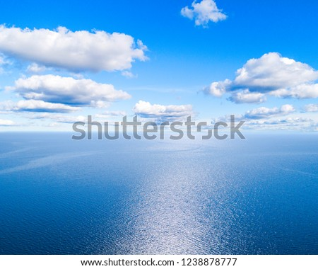 Aerial view of a blue sea water background and sun reflections. Aerial flying drone view. Waves water surface texture on sunny tropical ocean. Aerial photography. Birdseye. Sea, beach, sky, clouds. #1238878777