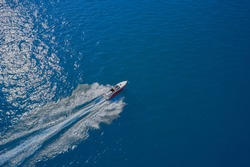 Aerial view of a boat in motion on blue water. Boat in the sun. Top view of a white boat sailing in the blue sea. Drone view of a boat sailing at high speed.