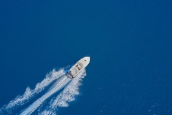 Aerial view of a boat in motion on blue water. luxury motor boat. Top view of a white boat sailing in the blue sea. Drone view of a boat sailing at high speed.