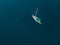 Aerial view of a boat moored in the Atlantic Ocean near the jagged shores and beaches of Lanzarote, Spain, Canary Islands