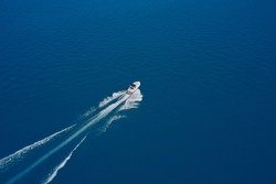 Aerial view of a boat with an awning in motion on blue water. Top view of a white boat sailing in the blue sea. luxury motor boat. Drone view of a boat sailing at high speed.