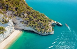 Aerial view of a Boat with tourists visiting a groat Puglia coast, Italy. Italian holidays in Puglia - Natural park Gargano with beautiful turquoise sea.