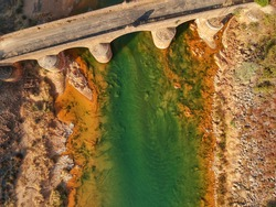 Aerial view of a bridge over odiel river in huelva, andalucia, spain, in a sunny day. green water and orange soil creating beautiful textures. taken with a drone, top down view