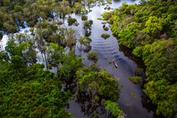 Aerial view of a canoe among the trees in the Amazon rainforest at the time of the river's flood.