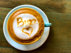 Aerial view of a cappuccino with buzz and heart design.