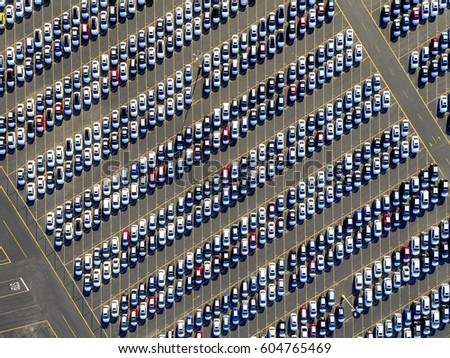 Aerial view of a car distribution centre, new cars parked in rows on a lot ready for sale,