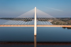 Aerial view of a central pillar of white cable-stayed suspension bridge above a river reflecting in smooth water