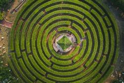Aerial view of a circular garden maze and green pavilion