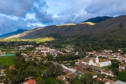 Aerial view of a colonial-style church and houses of the same style with mountains in the background in the town of Villa de Leyva. Colombia.