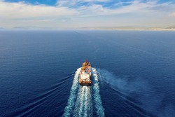 Aerial view of a container cargo vessel in full motion approaching the main land