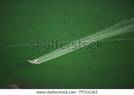 Aerial View of a crop duster spraying a farm field