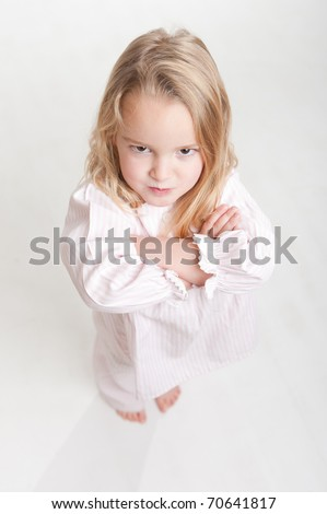 Aerial view of a cute little blonde girl with an angry expression in her pajamas
