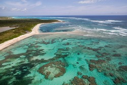 Aerial view of a deserted beach, coral formations and turquoise waters along the coastline on the Atlantic Ocean side of Cat Island, Bahamas.