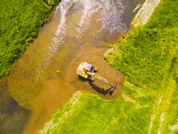Aerial view of a excavator digging on golden river. Prospecting new locality for mining. Heavy industry and environment. Ecological disaster. Water pollution.