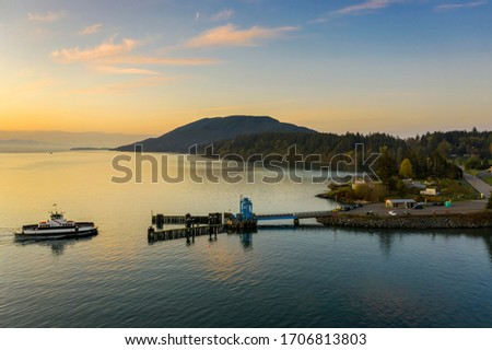 Aerial View of a Ferry Boat Landing at the Island Dock. Aerial shot of a small 21 car ferry landing at the Lummi Island ferry dock on a beautiful sunlit morning in the the Pacific Northwest, USA.