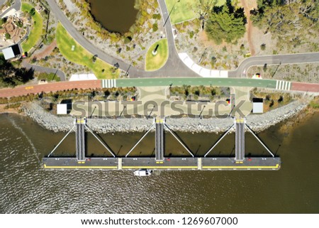 Aerial view of a floating jetty (Burswood Jetty) with the river below and colourful walkway and park behind in Perth Western Australia #1269607000