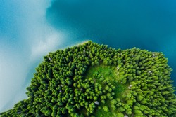 Aerial view of a forest lake. Aerial view of blue lake and green forests on a sunny summer day. Drone photography. Forest and lake border, Toned image from above. Coastline view from the drone.