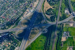 Aerial view of a highway and overpass with green forests and houses on a summer day.