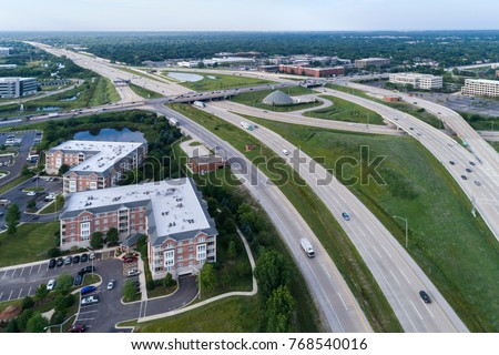 Aerial view of a highways, overpasses, ramps and buildings in a suburban Chicago suburban setting. #768540016